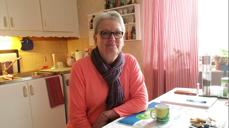 Anitha Fredriksson sitter vid sitt köksbord.