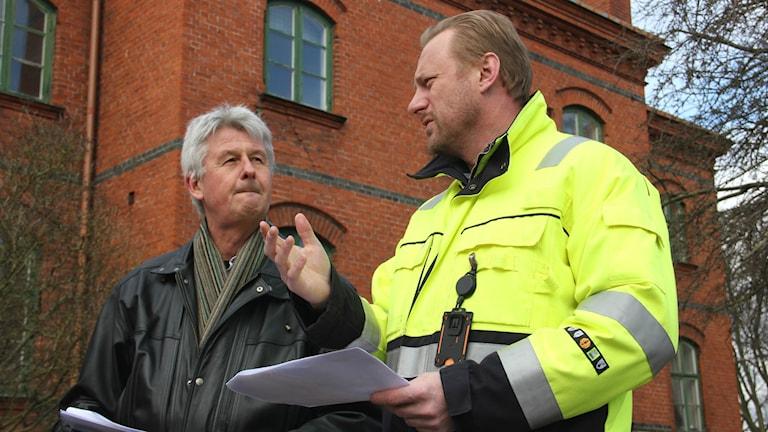 Projektledaren från Karlskrona kommun Anders Jaryd tillsammans med Affärsverkens Fredrik Fresell, framför en av de byggnader som snart ska rivas.