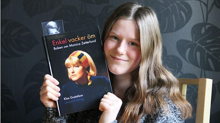 En ung tjej med långt hår håller i en bok om Monica Zetterlund