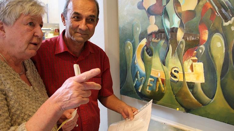 G Hassan Al Shaabe och Inger Persson pekar på en tavla med budskapet gemenskap.