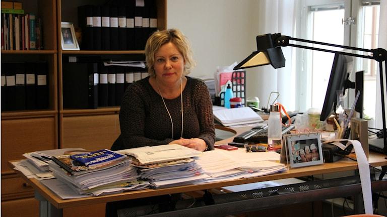 En kvinna sitter vid ett skrivbord.