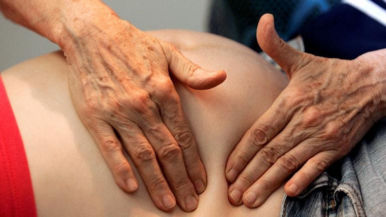En barnmorskas händer klämmer på en gravid mage.