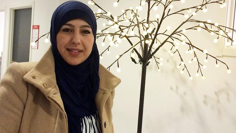 Sanaa Ahmad framför ett upplyst träd inne på SFI i Karlskrona.