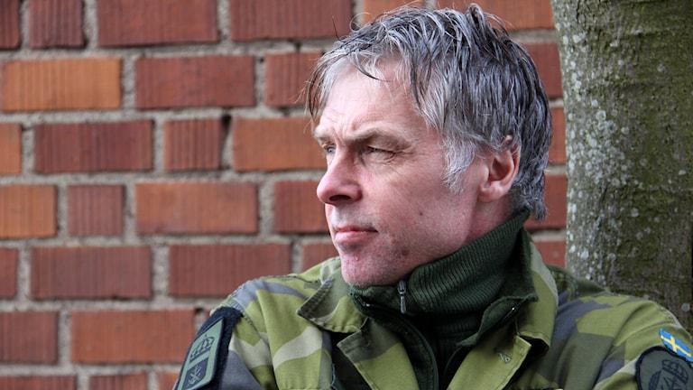 Peter Östling står framför en röd tegelvägg.