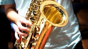 En person som spelar saxofon.