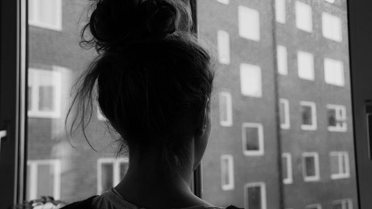 Silhuetten av en kvinna som står och tittar ut genom ett fönster.