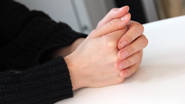 Ett par knäppta händer som vilar på en bordsskiva.
