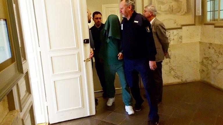 En av de åtalade förs in i rättssalen med handduk för huvudet.