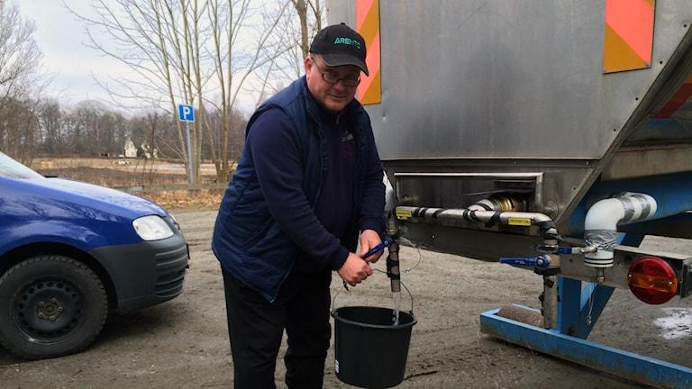 En man tappar upp vatten från en tank.