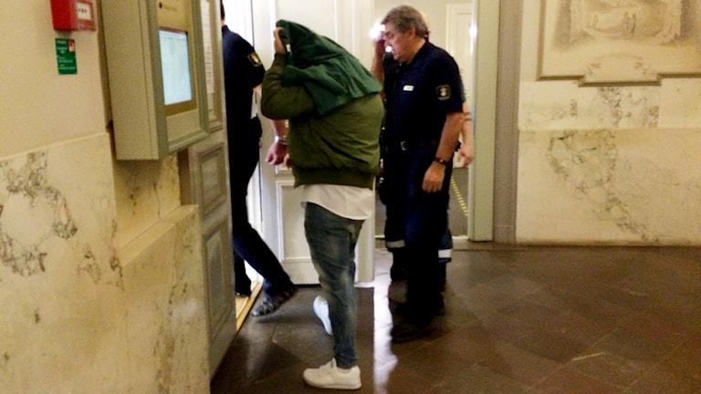 En av de åtalade i rättegången om guldrånet förs in i rättssalen me en handduk över huvudet.
