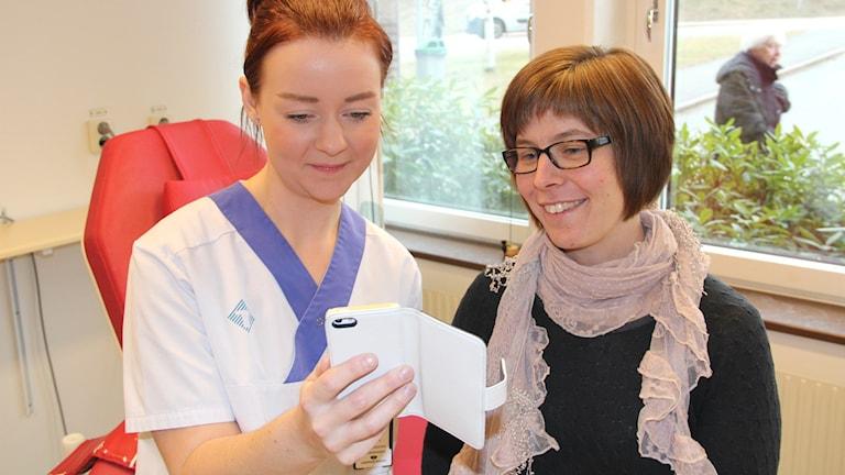 Hanna Sonesson och Anna Kronmar kollar in hur Sms-hälsningen ser ut i mobilen.