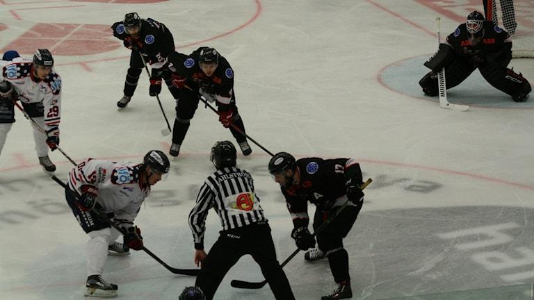 Domare och hockeyspelare i match.