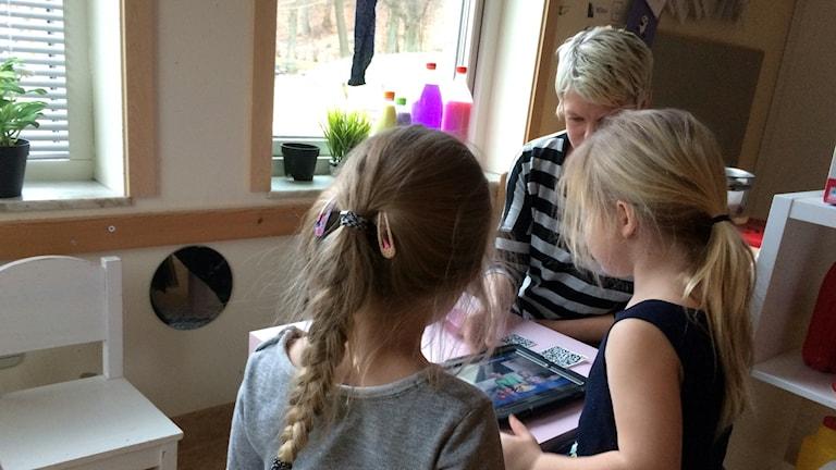 pedagogen Birgitta Germundal tillsammans med två av barnen på Hästö förskola.