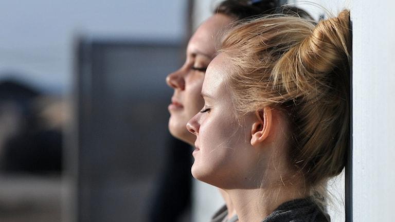 Två tjejer lutar sig tillbaka och njuter av solen.