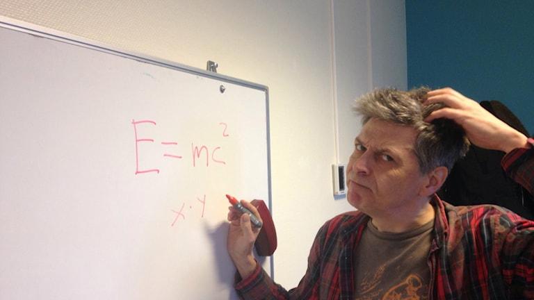 Man står framför white board och räknar matte