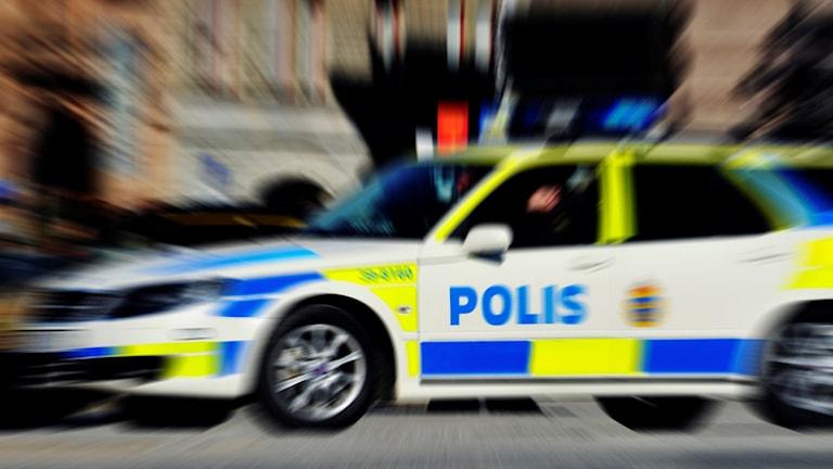 Suddig bild på polisbil under uttryckning.