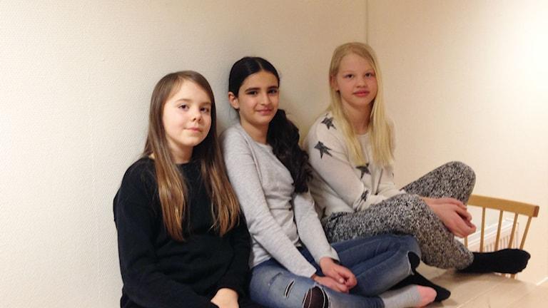 Tre elever sitter på ett bord med benen i kors.
