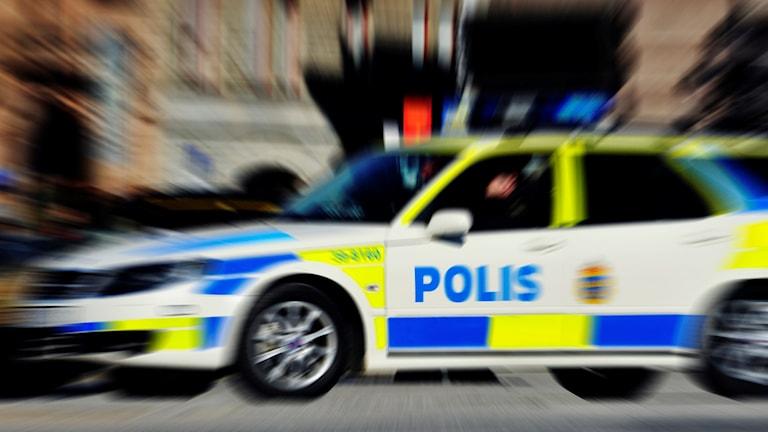 Bild på suddig polisbil under uttryckning