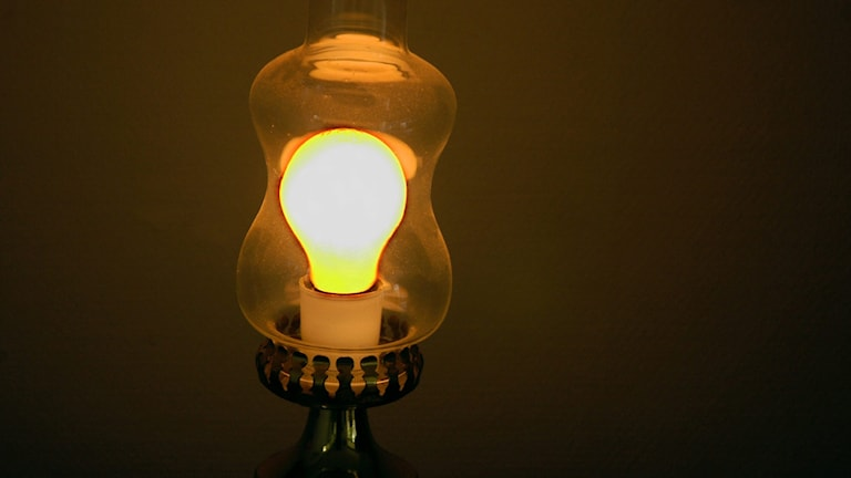 En klart lysande glödlampa med mörk bakgrund.