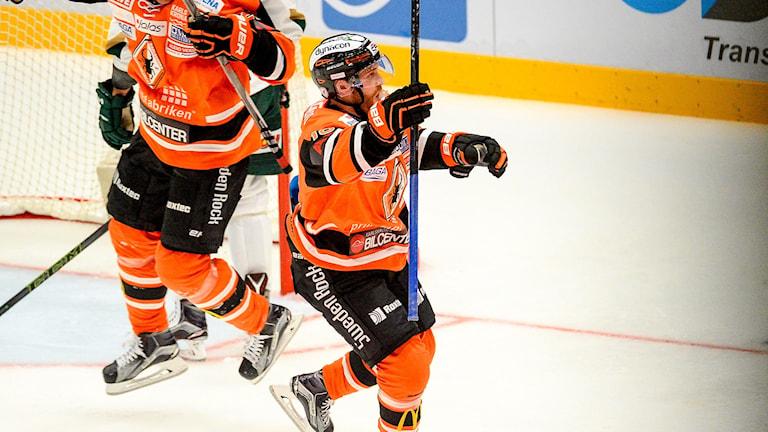 Jublande hockeyspelare framför mål.