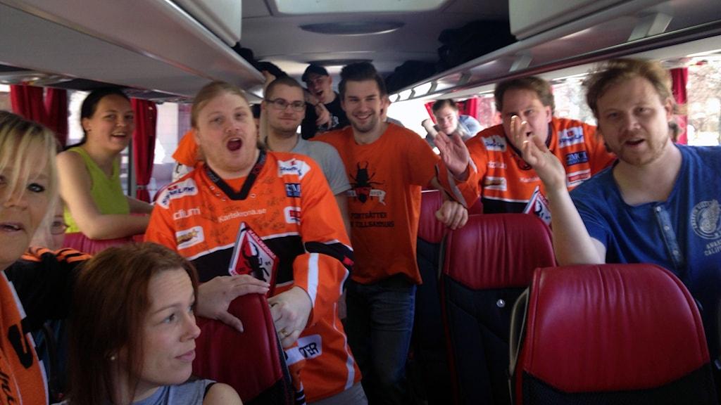 Supportrarna i Black bugs sitter i en buss och sjunger hejaramsor.