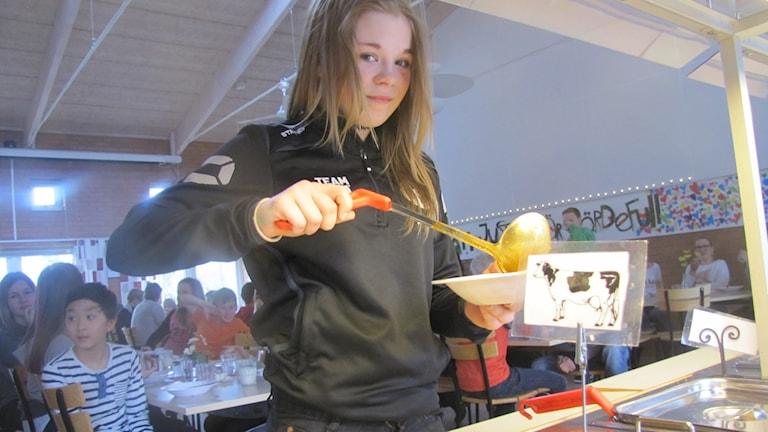 En elev häller upp soppa i en djup tallrik i en skolmatsal.