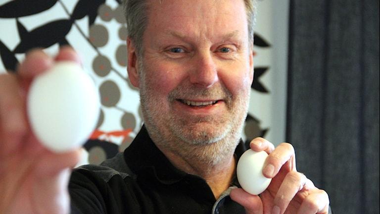 Tomas Håkansson, ledamot Blekinge Rasfjäderfäklubb håller upp två ägg.