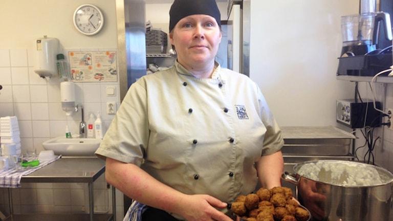 Matpersonal står i köket och håller i en behållare med köttbullar.