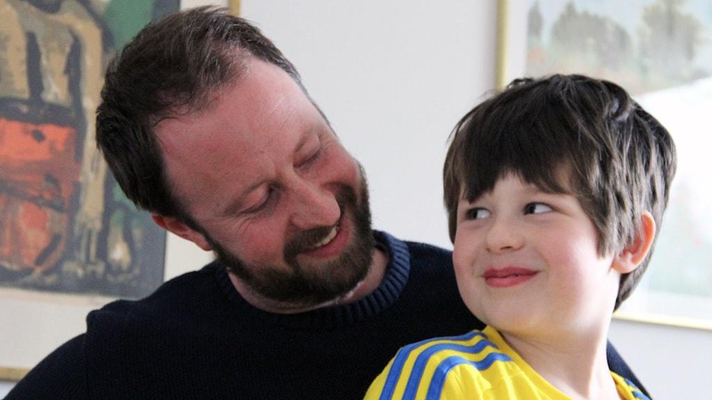 Dante Bergman sitter i sin pappa Mattias knä och ler mot honom.