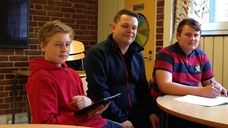 två elever och en lärare i en lektionssal tittar rakt in i kameran och ler.