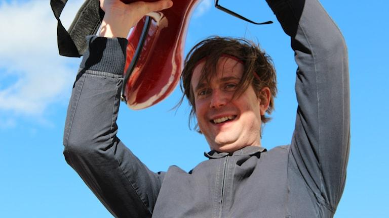 Timo Räisänen lyfter sin gitarr i skyn.