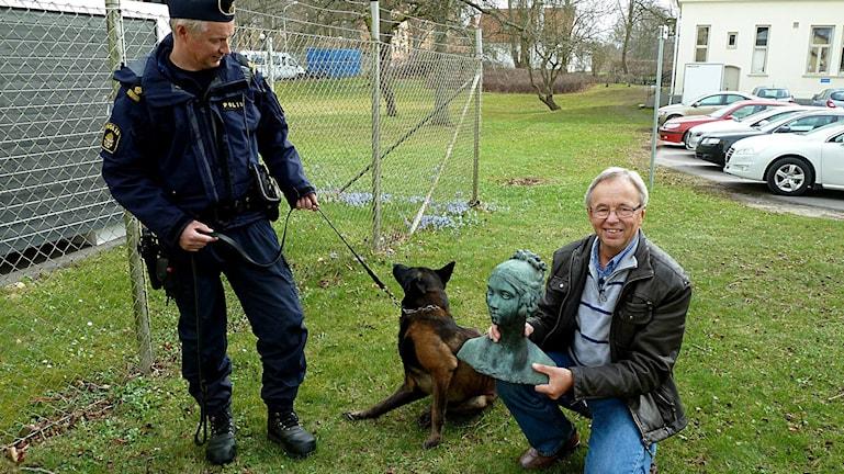 Polis Ronny Holmberg med hunden Ilska vid sidan om Jan Ottosson och Carl Eldh-bysten av Brita.
