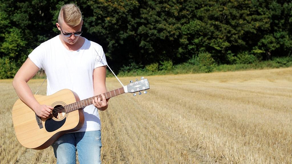 Albin Hultman går på en åker med en gitarr i handen.