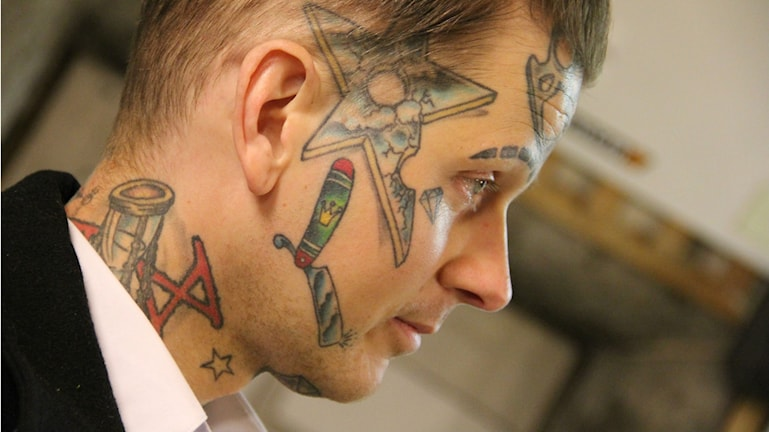 Närbild på en man i profil. Han har tatueringar i ansiktet.