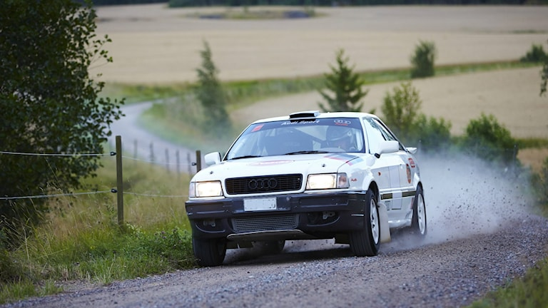 Rallybil längs en grusväg.
