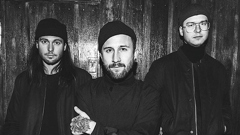 En svartvit bild på bandet moment med tre manliga medlemmar.
