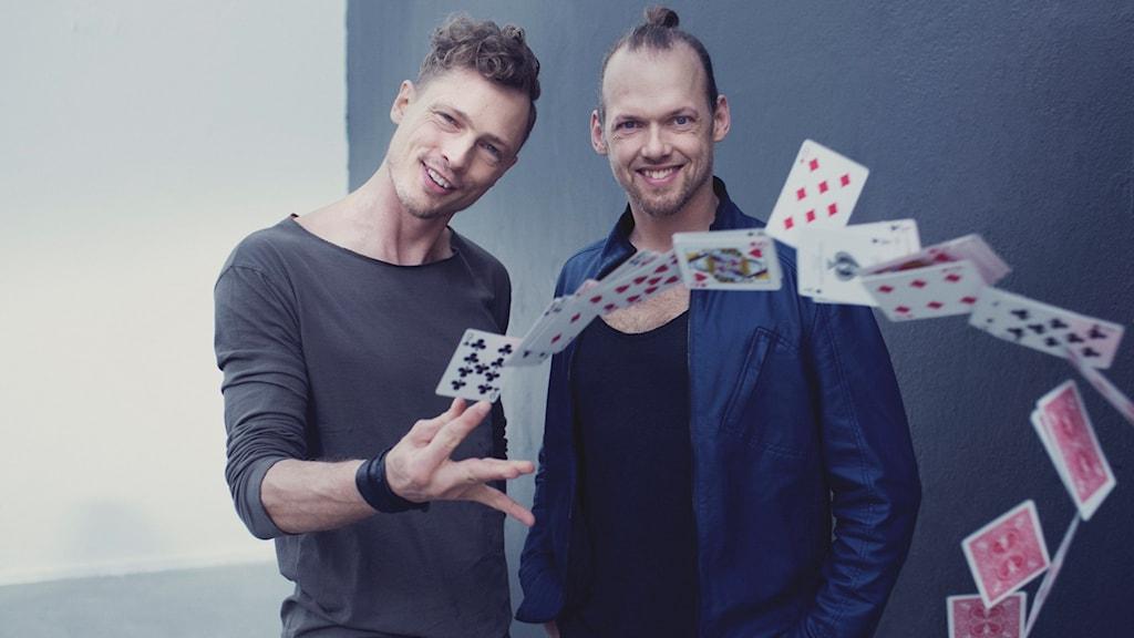 Peter Brynolf och Jonas ljung kastar spelkort mot kameran.
