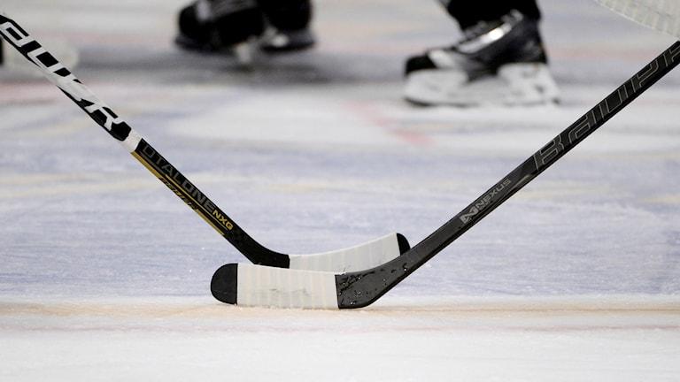 Två korsade hockeyklubbor på is och skridskror i bakgrunden.
