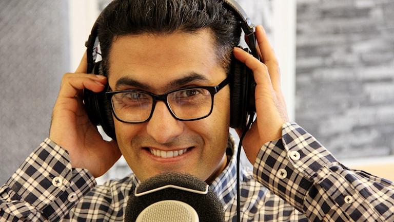Reportern Mansoor Yousefzai framför en mikrofon i studion