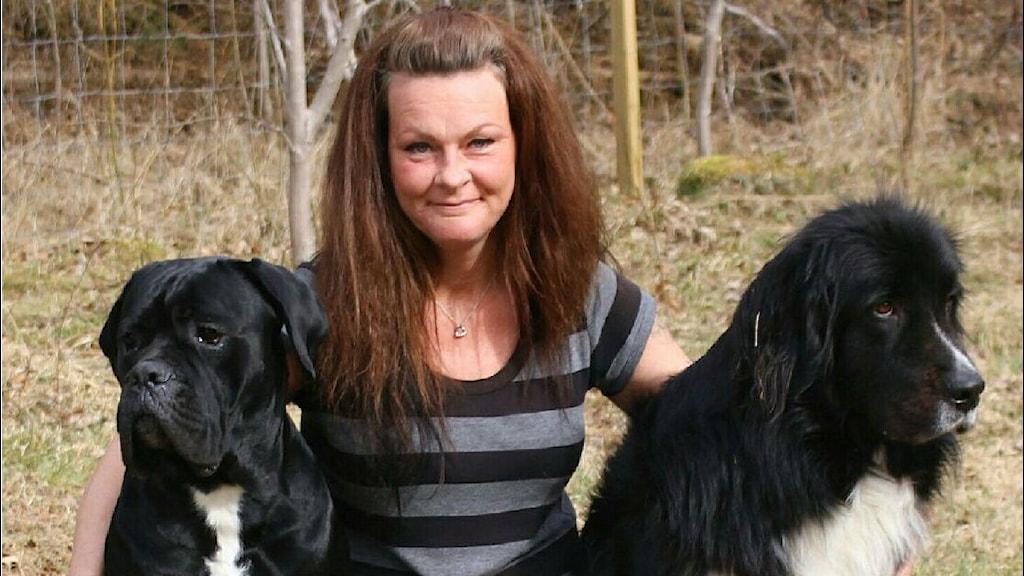En kvinna sitter med två stora svarta hundar bredvid sig.