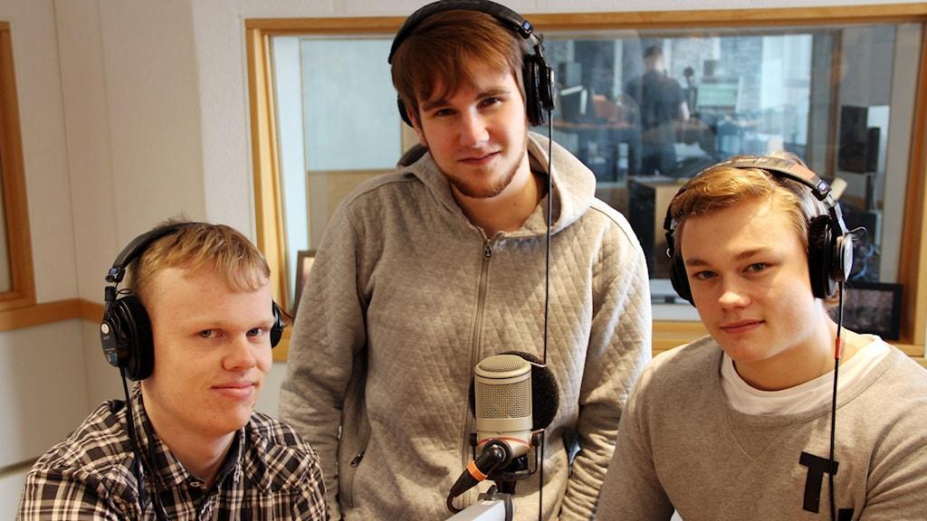 Tre killar framför en mikrofon i studion.