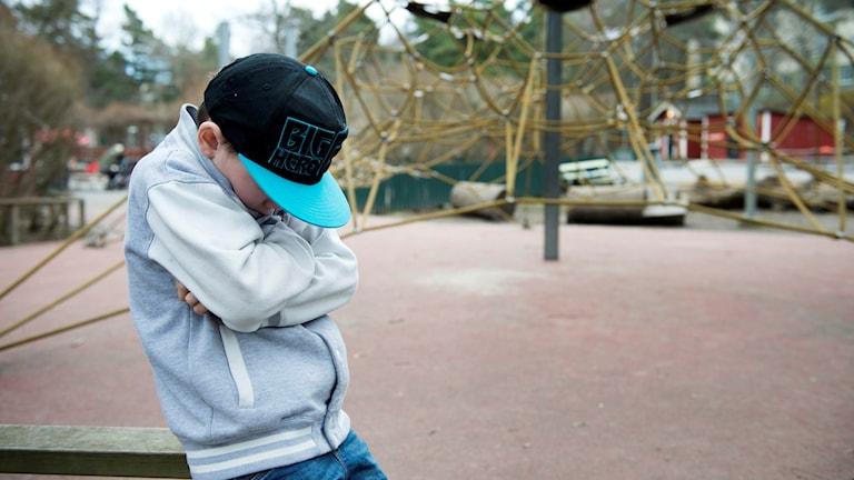 En pojke står med nedböjt huvud och med armarna i kors.