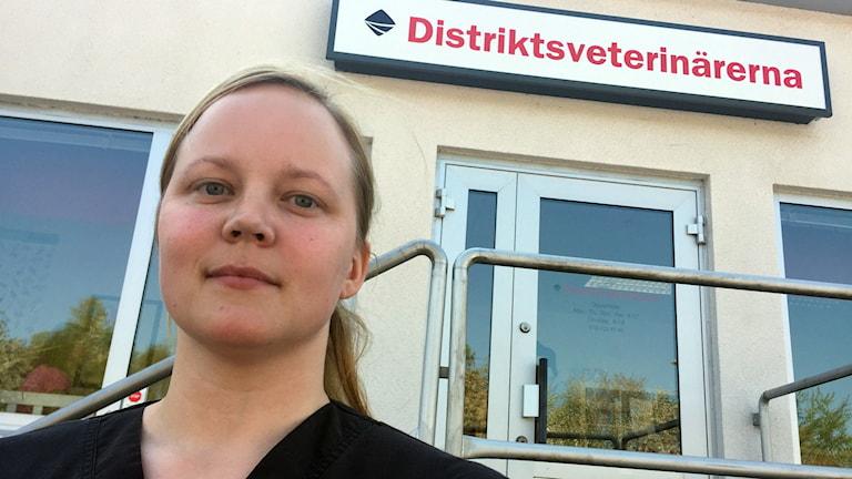 En bild på Amelie Andersson utanför distriktveterinärernas lokaler i Karlshamn.