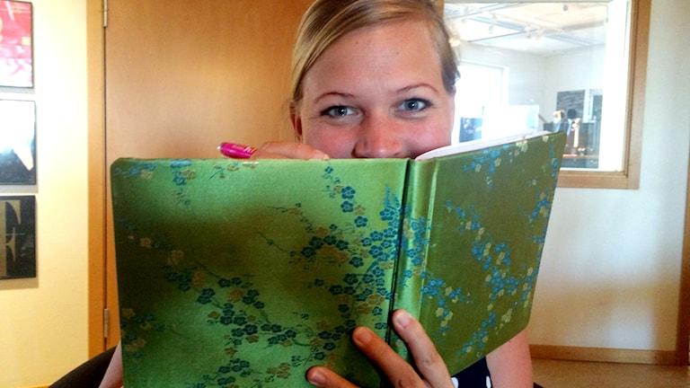 Rebecka Gyllin håller en grön dagbok framför ansiktet.