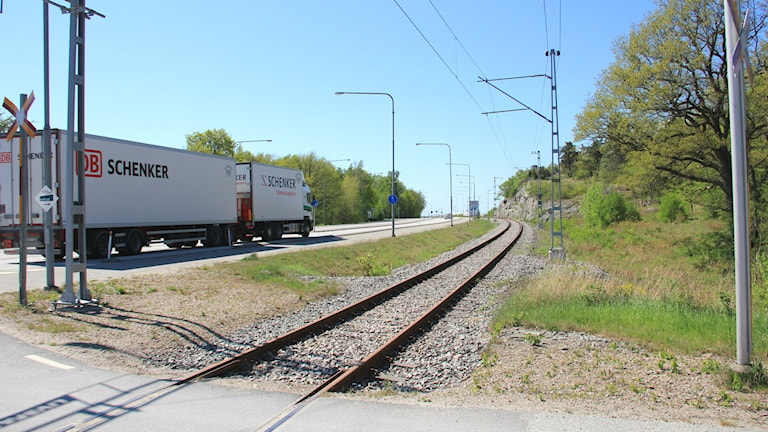 En lastbil kör intill ett tomt järnvägsspår
