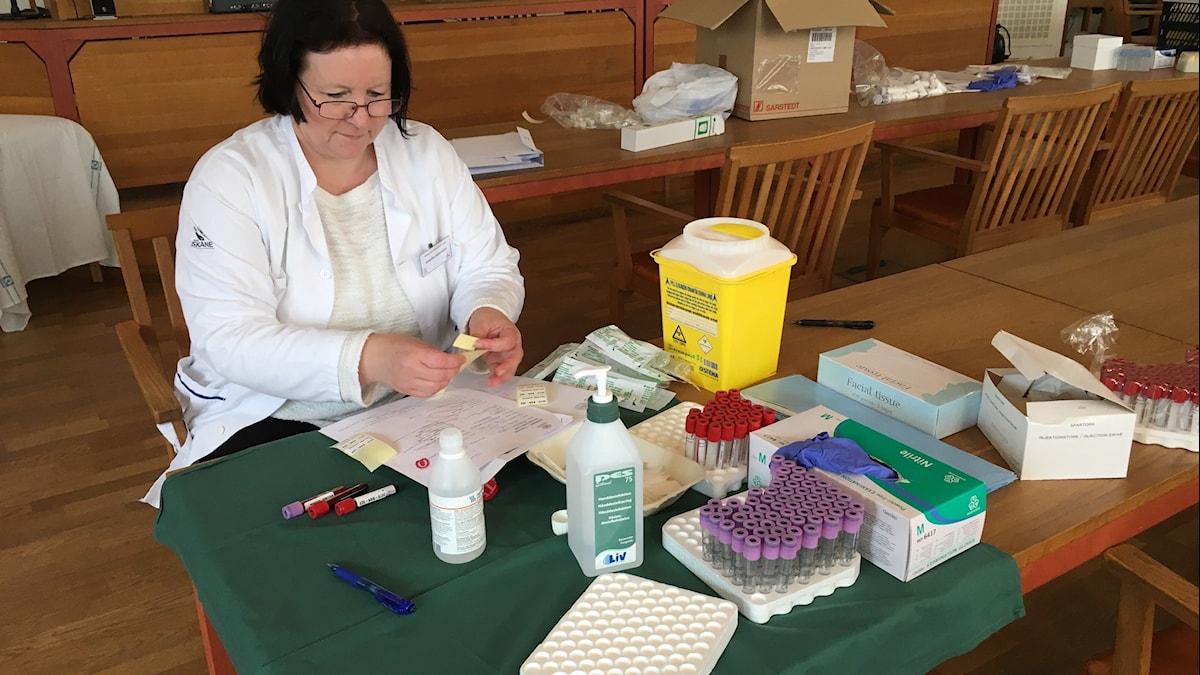 En kvinna sitter vid ett bord och märker upp blodprov.