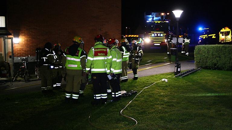 Räddningspersonal står i klunga och pratar med varandra. Reflexvästarna lyser i mörkret.