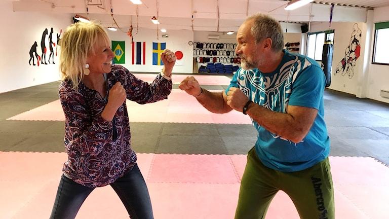 Susanne Håkansson och Per Emanuel låtsas slåss på en matta.