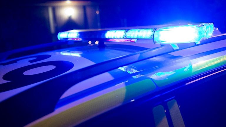 Taket på en polisbild med blåljusen igång.
