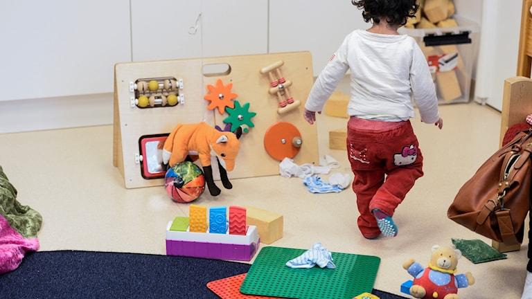 En bild på ett barn som leker på med leksaker i en förskolemiljö.